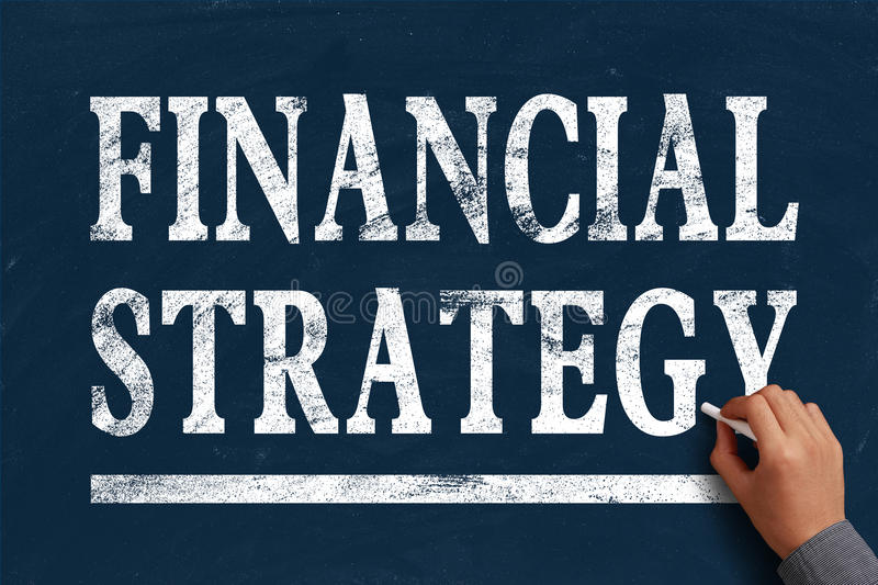 Financial strategy. Businessman is writing Financial strategy text on blue chalkboard royalty free stock photo
