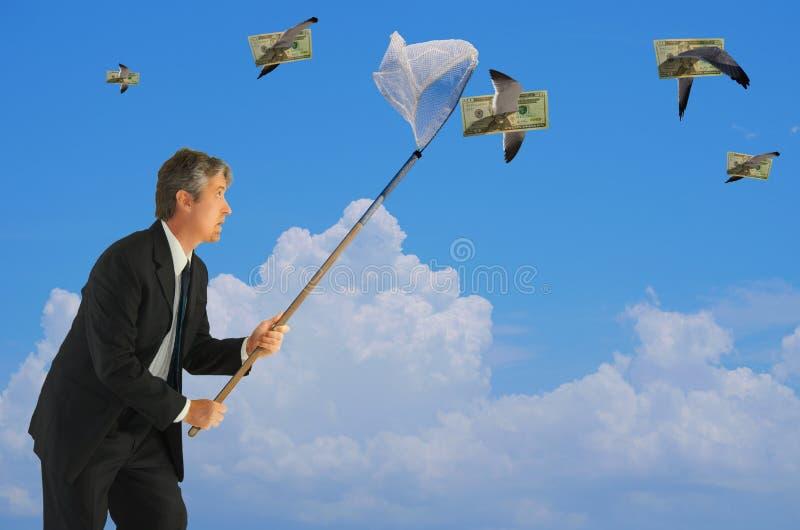 Man netting flying money financial success stock photos
