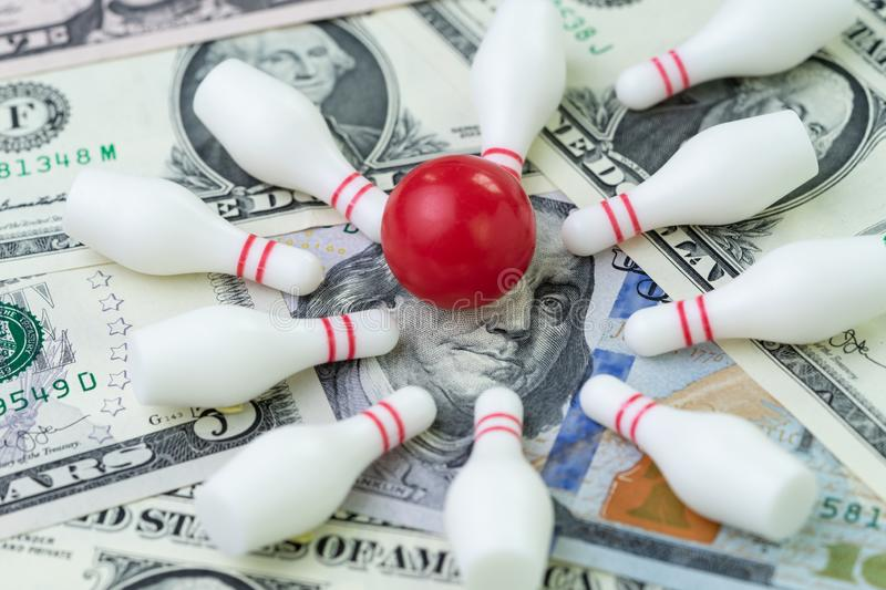 Financial success target concept, red winning bowling strike ball surround with knocked down pins on pile of US dollar banknotes stock images