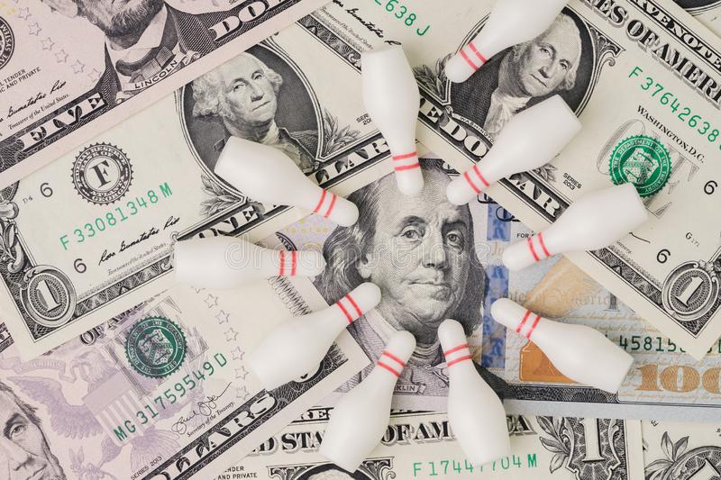 Financial success target concept, red winning bowling strike ball surround with knocked down pins on pile of US dollar banknotes stock photo