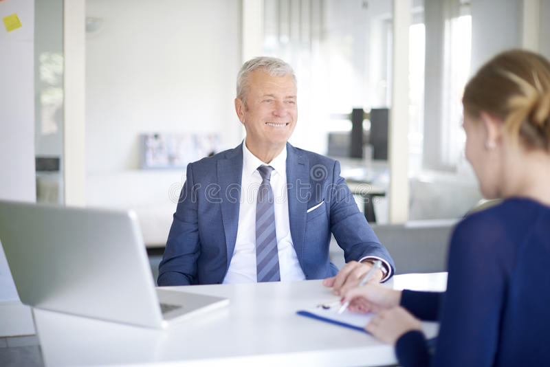 Financial team at work. Shot of a senior investment advisor businessman consulting with her young assistant while sitting at office and working on laptop royalty free stock photo