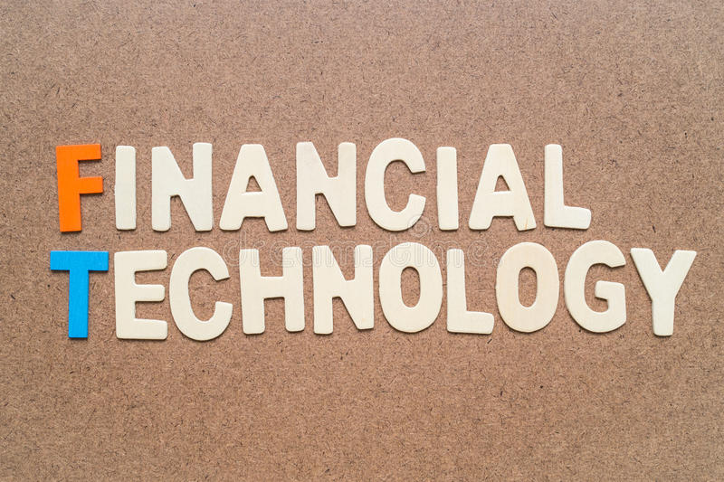 Financial Technology wording on brown background. Text 'Financial Technology' wording on brown background - FinTech colorful words made from wood royalty free stock photo