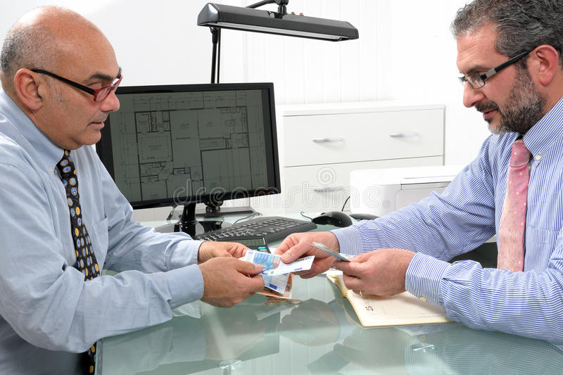 Financial transaction between businessmen. Businessmen engaged in a financial transaction with banknotes of the Euro currency stock photography