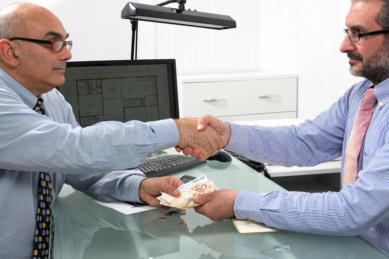 Financial transaction between businessmen. Handshake between businessmen engaged in a financial transaction with banknotes of the Euro currency royalty free stock photos