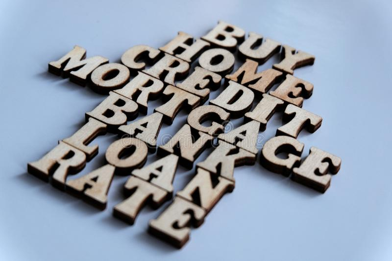 Financial words from wooden letters. House symbol or arrows. Selective focus. Shallow depth of field. Purchase, house, loan, bank. Financial words from wooden royalty free stock photos