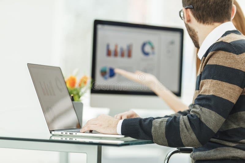Financie al especialista que trabaja en el ordenador portátil con las cartas y los esquemas de márketing financieros foto de archivo libre de regalías