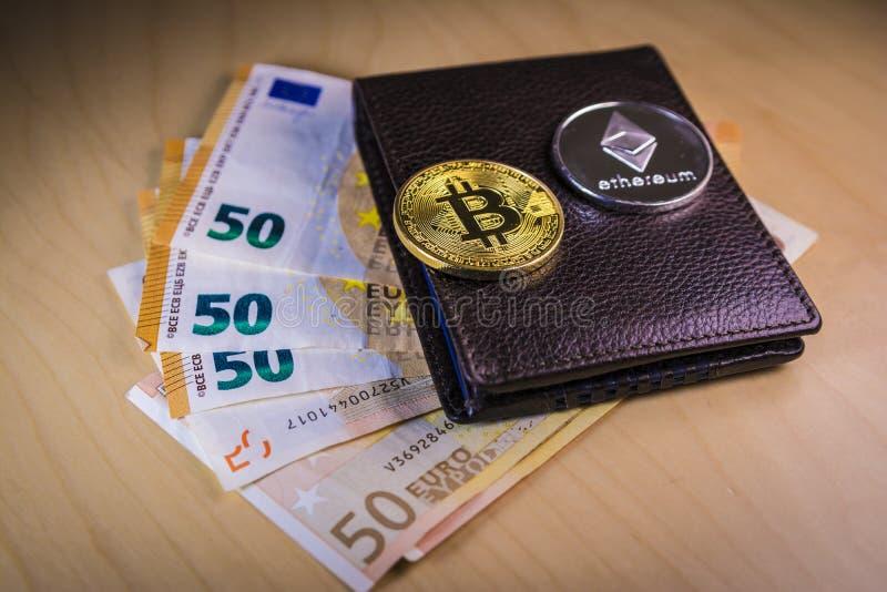 Financieel concept met fysieke bitcoin en ethereum over een portefeuille met Euro rekeningen stock foto's