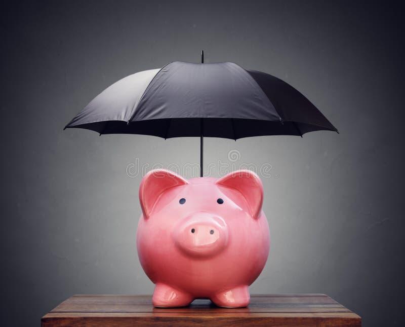 Financieel verzekering of beschermingsspaarvarken met paraplu royalty-vrije stock afbeeldingen