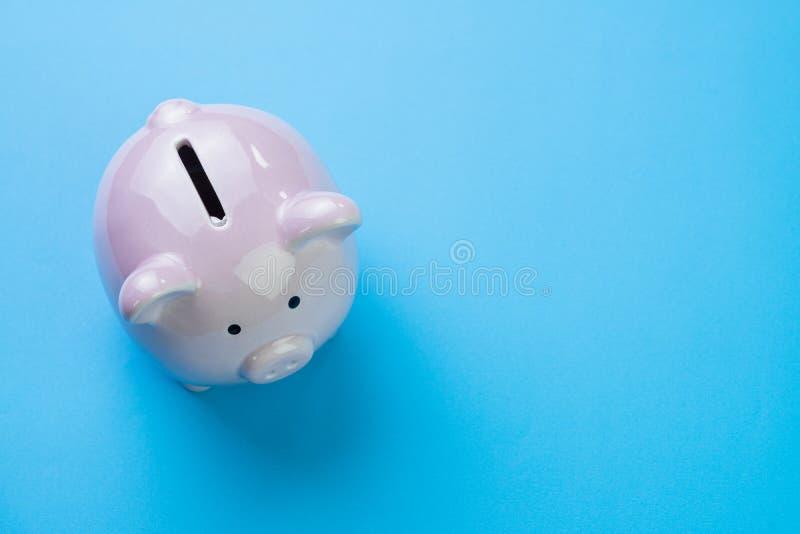 Financier, l'épargne, budget, coût ou concept d'investissement, tirelire heureuse blanche sur le fond bleu propre avec l'espace d image stock