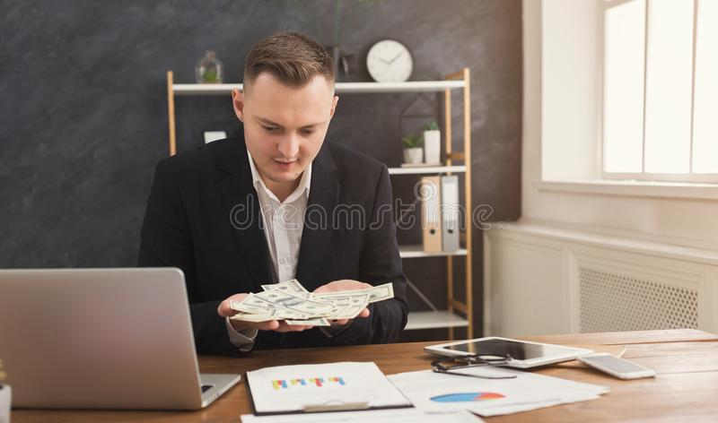 Financier man sitting in office and holding money in hand. Serious male financier sitting at office table and holding money in hands. Man counting his income stock photo