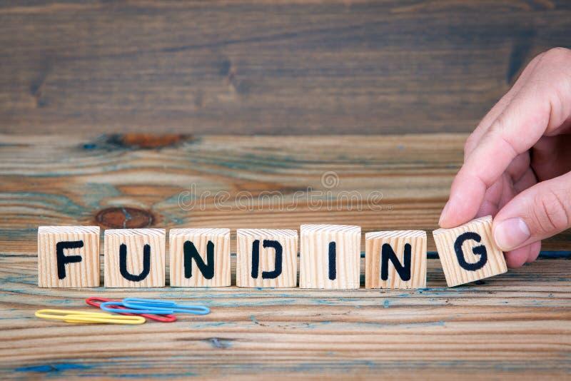 financiering Houten brieven op het bureau Zaken en de achtergrond van de geldinvestering stock afbeeldingen