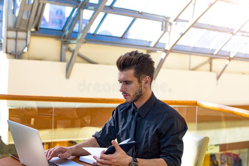 Financiero acertado del hombre serio que usa el libro de texto y el ordenador portátil, sentándose en compañía imagen de archivo libre de regalías