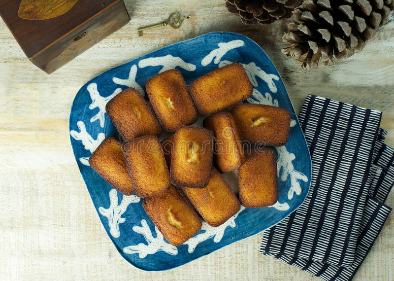 Financiers. Aerial view of plate of golden financiers (or almond mini cakes) for afternoon snack with tea caddy royalty free stock photography