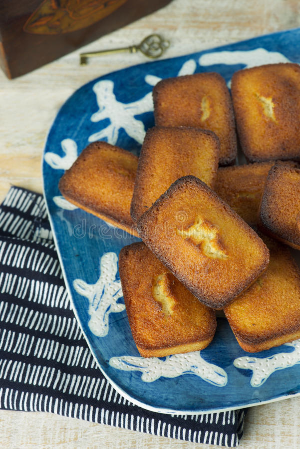 Financiers. Close up shot of golden financiers (or almond mini cakes) for afternoon snack with tea caddy stock image