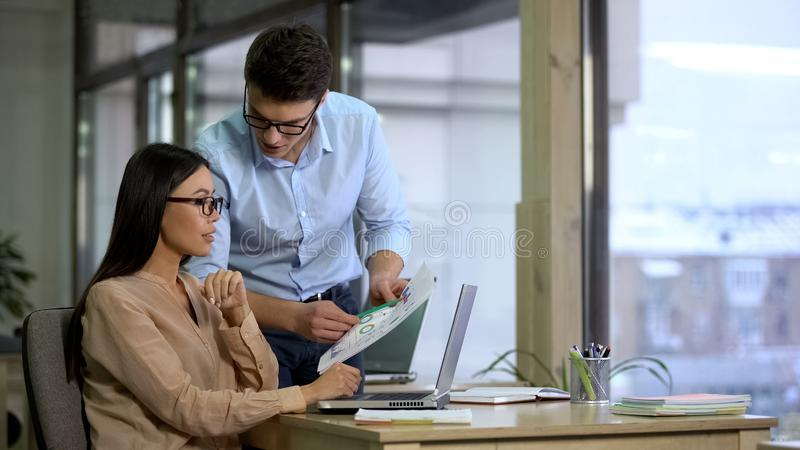 Financiers of large company comparing supply and demand graphs before reporting. Stock photo royalty free stock image