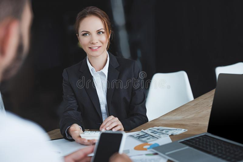 Financiers looking at each other and holding smartphone and calculator. In office royalty free stock photography