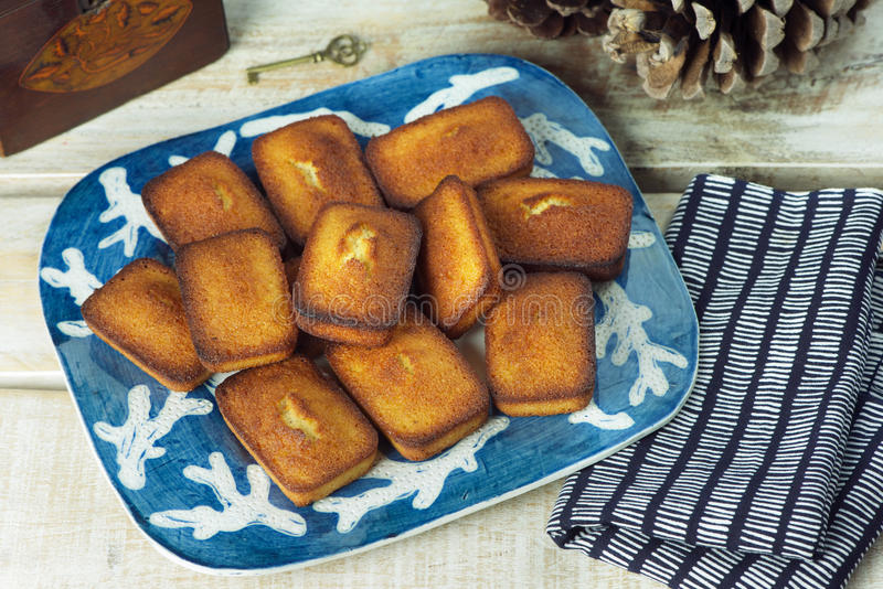 Financiers. Plate of golden financiers (or almond mini cakes) for afternoon snack royalty free stock photo