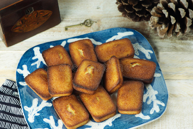 Financiers. Plate of golden financiers (or almond mini cakes) for afternoon snack with tea caddy royalty free stock photo