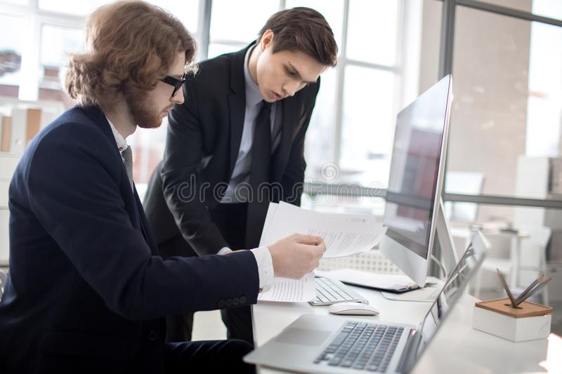 Financiers at work. One of young financiers showing colleague some paper or contract royalty free stock photo