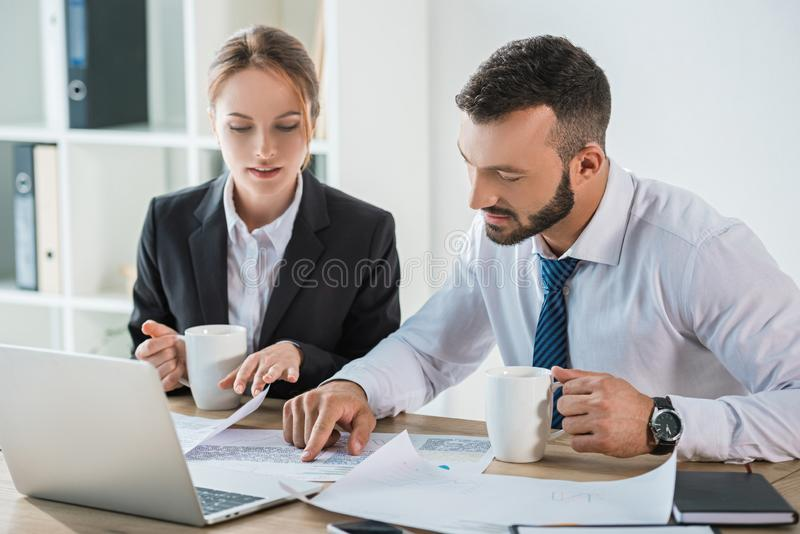 Financiers working with documents during coffee break. In office stock images