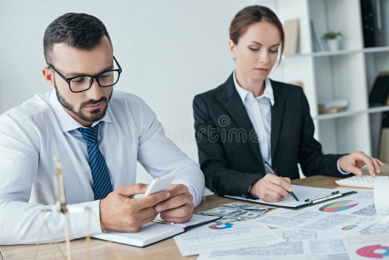 Financiers working with documents and using smartphone. In office royalty free stock photo