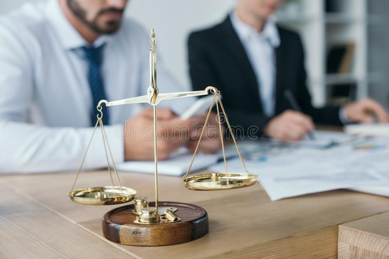 Financiers working in office with golden scales. On foreground stock images