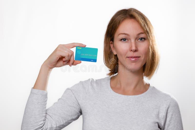 Finans och bank Porträtt av en ung blond kvinna som innehar ett bankkort Vit bakgrund Kopiera utrymme arkivbild