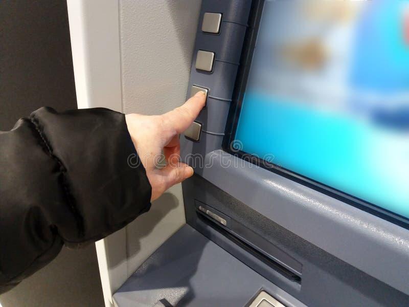 Finans-, pengar-, bank- och folkbegrepp - som är nära upp av händer som väljer alternativ på atm-maskinen arkivbild