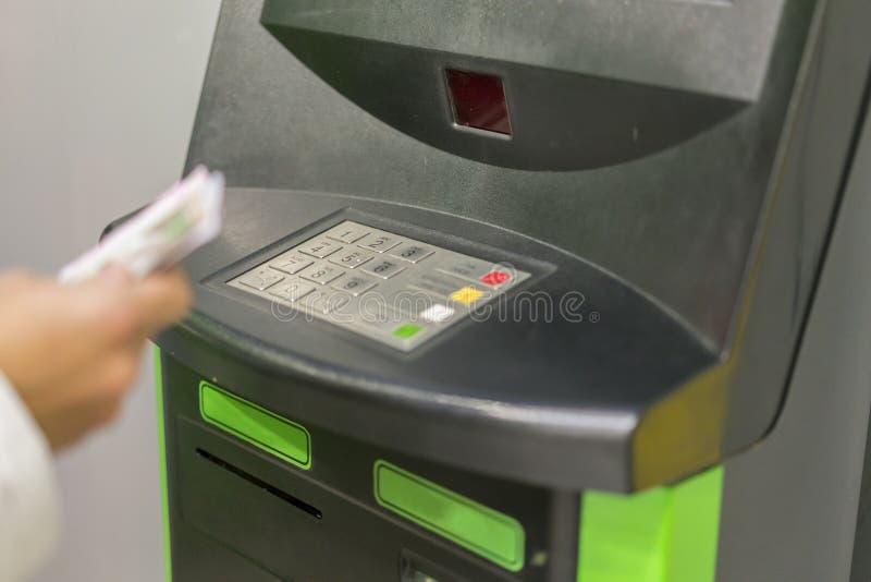 Finans-, pengar-, bank- och folkbegrepp - som är nära upp av handen med plånboken som återtar kassa på atm-maskinen Hand med peng arkivbilder