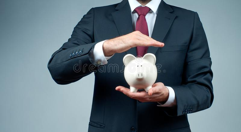Finansbesparingbegrepp Affärsmannen i dräkt är den hållande spargrisen arkivbild