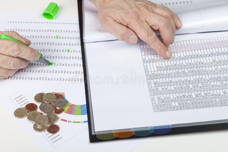 Finansiär på skrivbordet som korshänvisar huvudböcker för några försäljningar royaltyfria foton