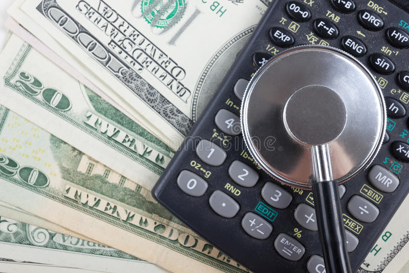 Finansiell analys, revision eller redovisning - stetoskop över en räknemaskin och dollarräkningar Medicinska kostnader, finansiel royaltyfri foto