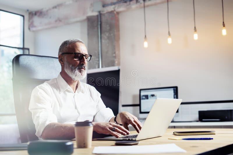 Finansiell analytiker för mellersta ålder som bär klassiskt exponeringsglas och arbete på den wood tabellen i modernt inredesignk royaltyfri fotografi