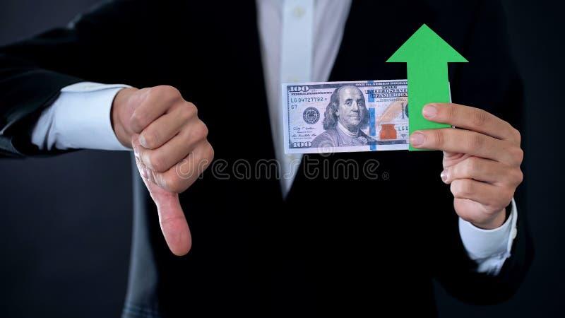 Finansiell konsulent med dollarsedlar som ner visar tummar och den gröna pilen royaltyfri bild