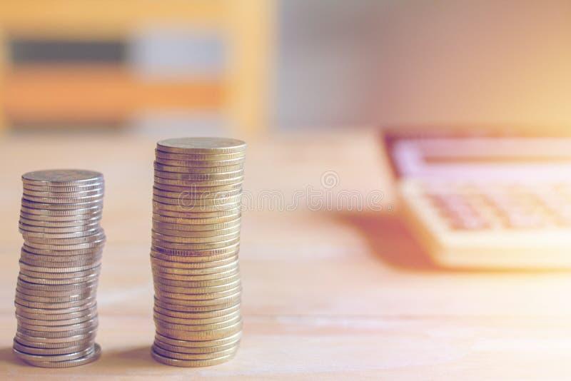 Finansiell räkenskap och mynt på tabellen med solnedgång arkivfoton