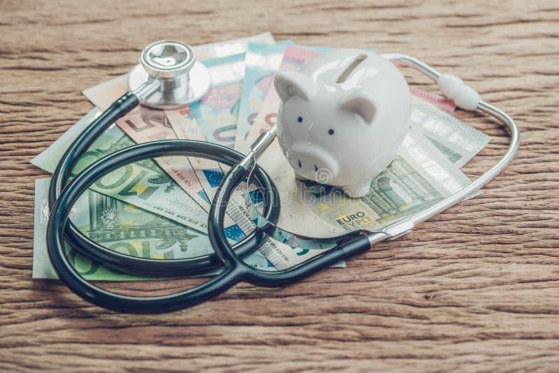 Finansiell vård- kontroll eller ekonomiskt begrepp för EU, sparande vit spargris med stetoskopet på högen av eurosedlar på trätab fotografering för bildbyråer