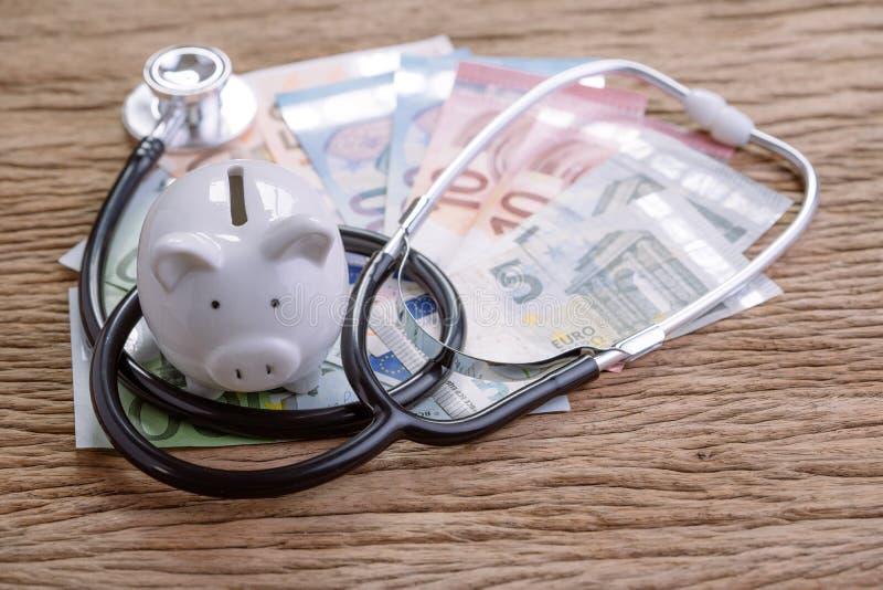 Finansiell vård- kontroll eller ekonomiskt begrepp för EU, sparande vit spargris med stetoskopet på högen av eurosedlar på trätab arkivbild