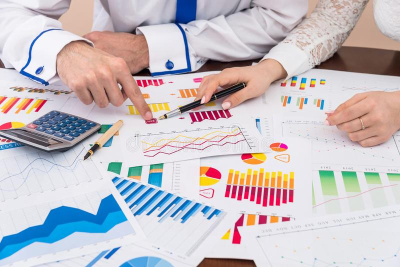 Finansiella analytiker som arbetar med affärsgrafer och diagram arkivfoton