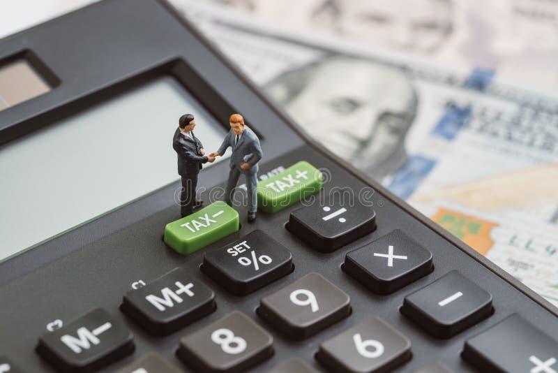 Finansiella skattesänkningar eller förminskar begreppet, miniatyrfolkaffär royaltyfria bilder