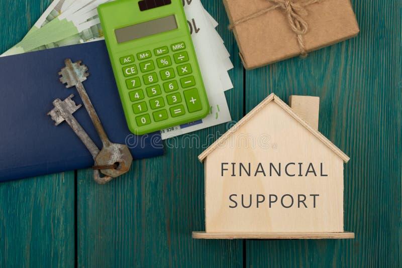 finansiellt hj?lpande begrepp - litet hus med textekonomisk hj?lp, tangenter, r?knemaskin, pass, pengar royaltyfria foton