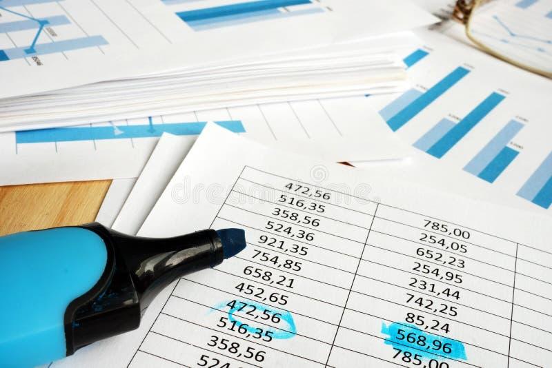 Finansiellt revidera för företag Legitimationshandlingar med grafer och markören arkivfoton