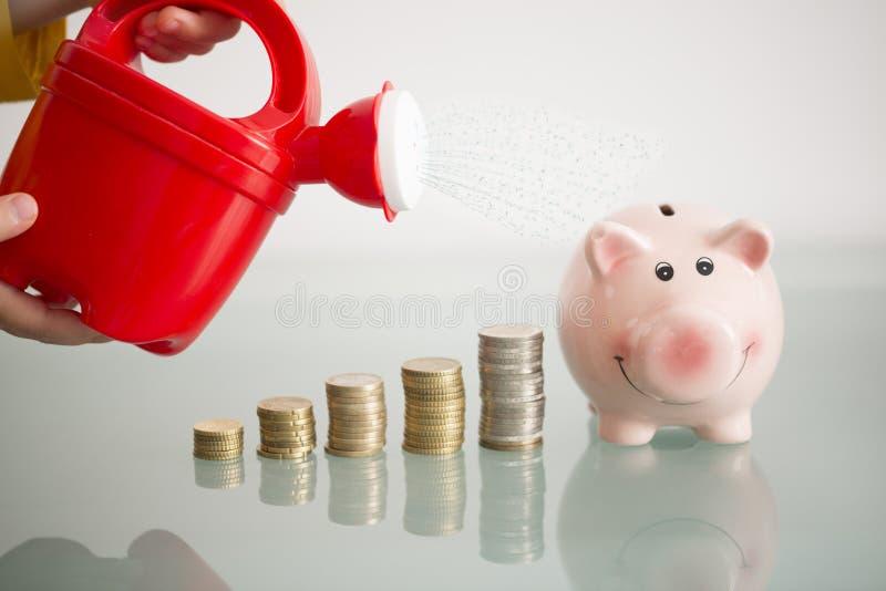 Finansiellt utbildningsbegrepp för ungar med unges händer som bevattnar stigande högar av pengar och piggybank arkivbilder