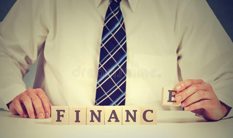 Finansmarknadbegrepp Affärsmannen räcker att ordna träkvarter med ordfinans arkivfoto
