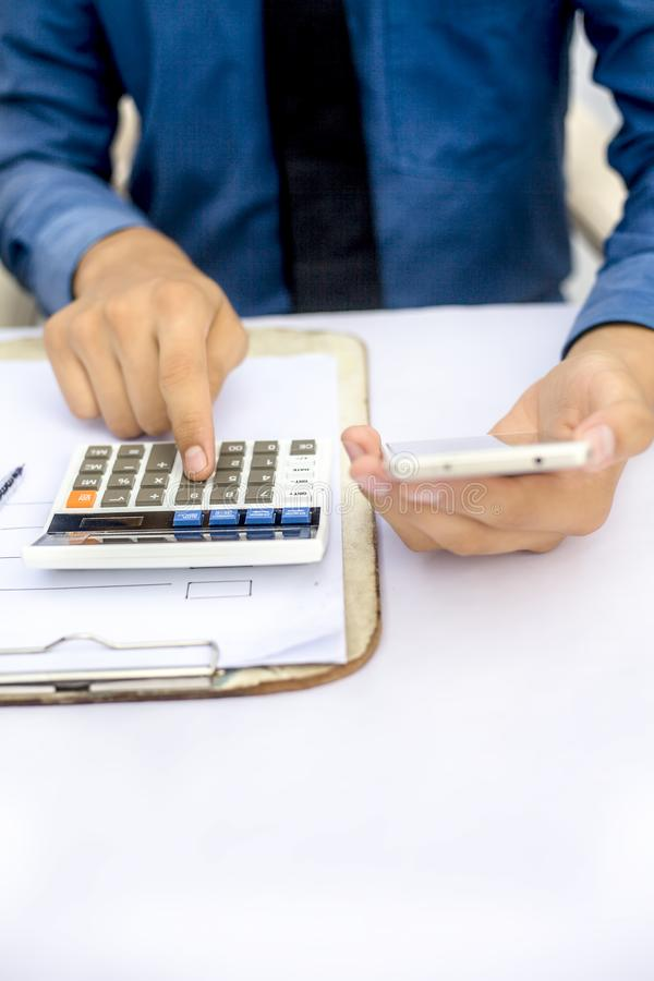 Finanspersontabell eller arbetsplats slut upp ett skott, medan han gjorde något finans och lån-släkt arbete med mobiltelefonen, c arkivfoto
