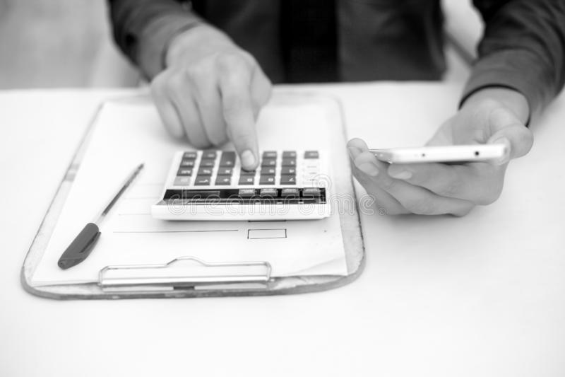Finanspersontabell eller arbetsplats slut upp ett skott, medan han gjorde något finans och lån-släkt arbete med mobiltelefonen, c fotografering för bildbyråer