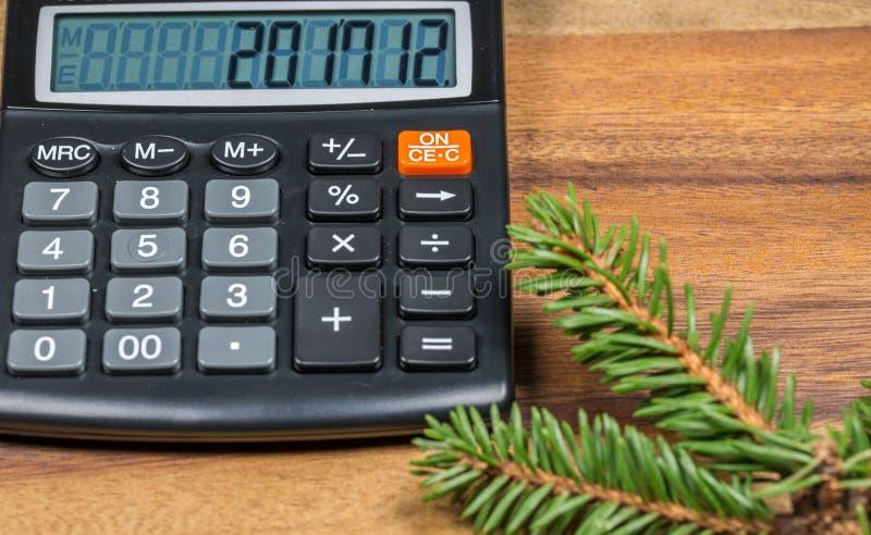 Finansräknemaskin med nummer för nytt år på skärm och granträdfilial close upp royaltyfria foton