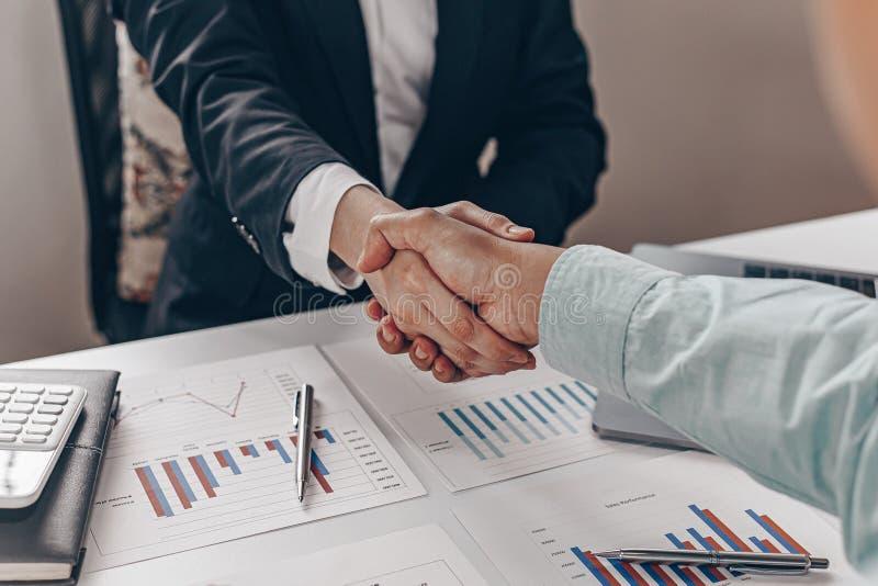 Finansrevisorer och finansmarknadsmäklare som skakar hand för att gratulera till den tvåsiffriga fastighetsprestandan. royaltyfri bild