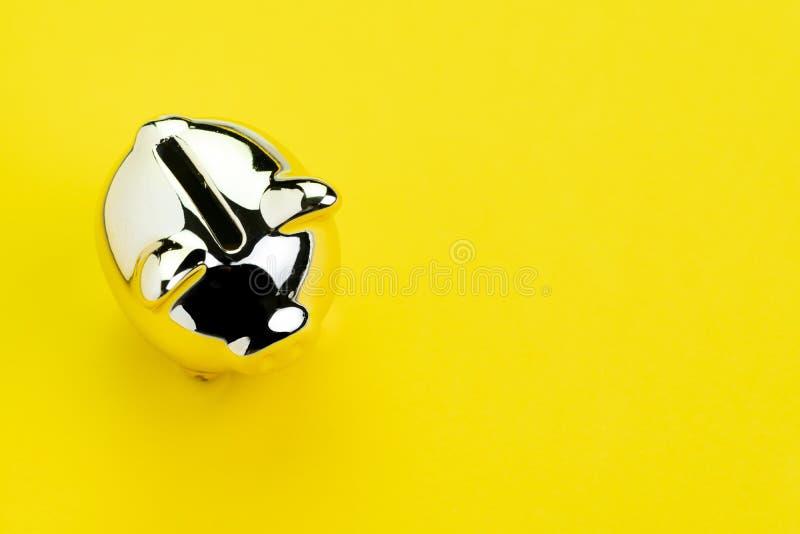 Finanza, attività bancarie, risparmio o concetto di investimento, porcellino salvadanaio d'argento brillante su fondo giallo soli fotografia stock libera da diritti
