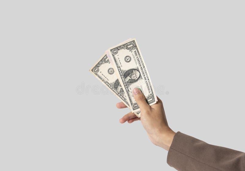 Finanza dei soldi di offerta di concetto del dollaro della tenuta della mano dell'uomo d'affari Isolato su priorità bassa grigia fotografia stock libera da diritti