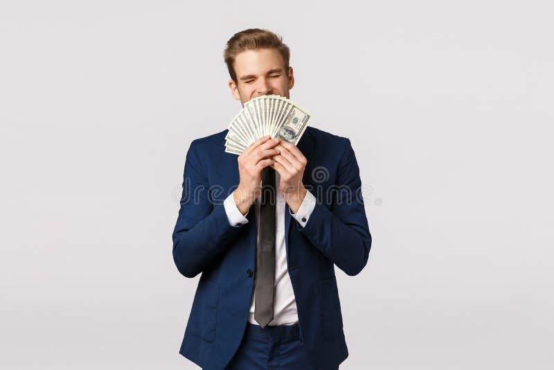 Finanza, economia e concetto di impresa Un giovane uomo d'affari di successo in completo, con molti soldi in mano, annusa immagine stock